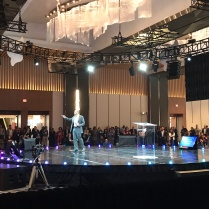 A man onstage in a hotel ballroom