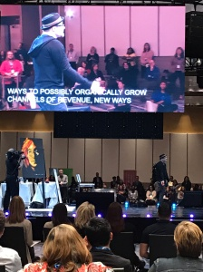 """Captions on the screen read: """"Ways to possibly organically grow channels of revenue, new ways..."""" Artist stands onstage with a speed-painted portrait of John Lennon"""