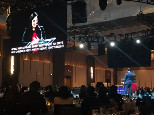 """A woman speaking onstage. Captions on the screen read """"Going and striving to be the future our children need and deserve, that's right."""""""