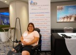 """A woman in a wheelchair sits in front of the """"This Is Disability"""" banner"""