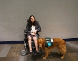 A woman in a wheelchair smiles with her service dog at her feet