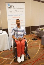 """A man in a wheelchair poses in front of the """"This Is Disability"""" banner"""