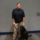 A man stands with his service dog at his feet