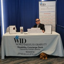 One WID staff member sits behind a desk with a service dog poking her head out front under the table cloth