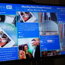 A large screen shows many different AEO conference tweets, including one by WID