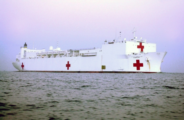 A large ship in a body of water. The ship is white with red crosses, signifying it has medical services.
