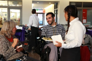 Two people in wheelchairs and one server smiling and laughing together