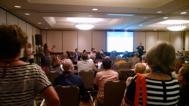 A crowded room with several presentation screens, an ASL interpreter, and captioning on the screens