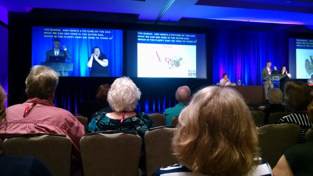 Link to HLAA Convention 2018 article; image of a man speaking to the audience, captions onscreen to his right, an ASL interpreter woman to his left