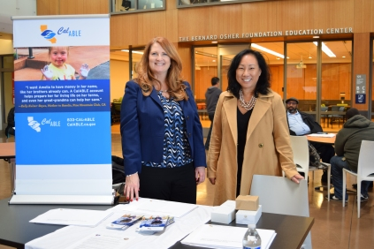 Two women smiling behind information table with CalABLE sign and brochures.
