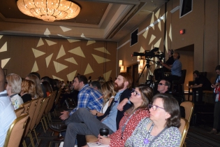 A row of audience members listening