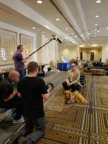 A man and his service dog sit across from a 3 person camera crew