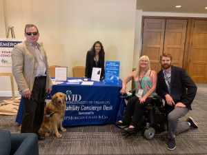 4 people and a service dog pose in front of WID table