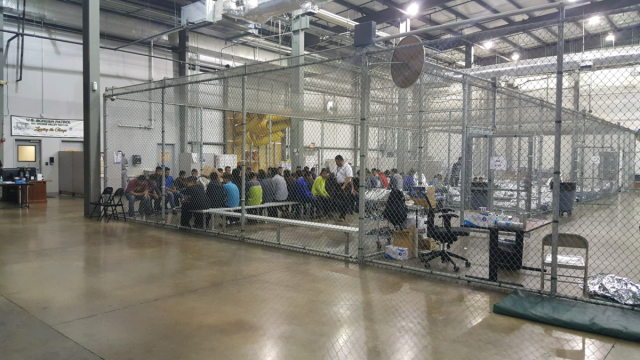Dozens of latinx immigrants sitting on benches inside of large chain-link cages