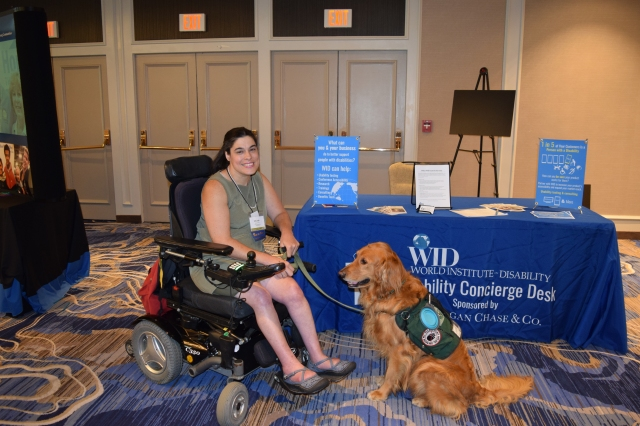A white woman using a power wheelchair smiles with her mobility service dog, a Golden Retriever