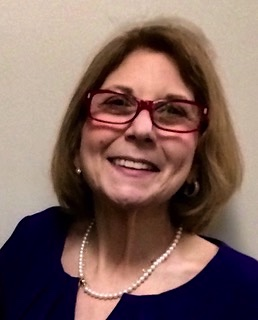 Marcie Roth smiling. Marcie is a white woman with light brown hair, wearing red glasses.