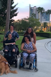 4 people in front of city skyline. 2 people are in wheelchairs (one manual, one electric) and two people are standing.
