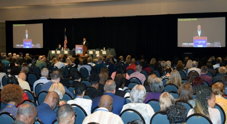 Large audience seated in theater-style rows of chairs, watching a man speak at a podium. Captions are shown on large screen to the left and right of the stage.
