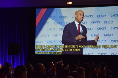 """Booker speaking, visible on huge screen with captions. Captions read, """"When I came to the Senate it was literally the least diverse place I had ever seen. And I'm not joking"""""""
