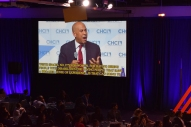 """Booker speaking passionately projected onto a large screen with captions. Captions read, """"...white spaces, no, it's for women, for having hiring people with disabilities, for having people that have a broader sense of experience, is that can bring to..."""""""