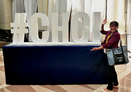 "Daya smiles and poses with her arms extended towards a large sign that says ""#CHCI"""