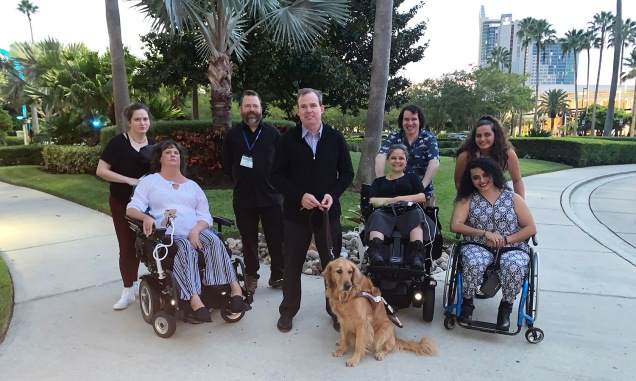 8 people and one service dog pose together. 2 people are in powerchairs, one person is using a manual wheelchair, and 5 people are standing.