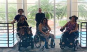 5 people posed in front of large window. 2 are standing, 2 are using powerchairs, and one person is using a manual wheelchair. Large Palm trees can be seen through the window.