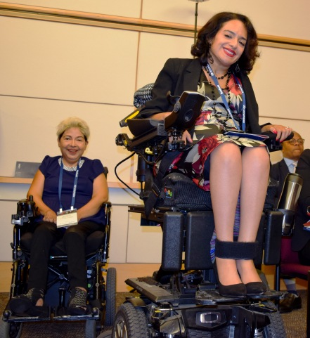2 women sitting in electric wheelchairs and smiling.