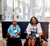 "2 women in electric wheelchairs smile in front of a large ""#CHCI"" sign."