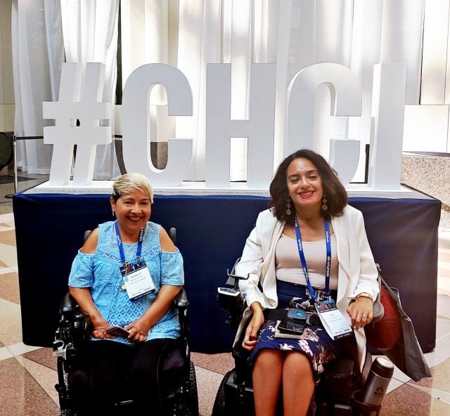 2 women in electric wheelchairs smile in front of a large