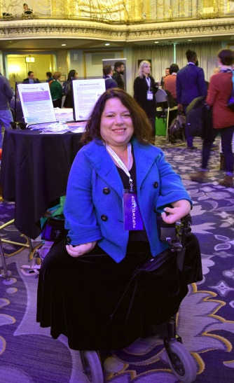 A woman with shoulder-length brown hair smiling brightly and posing in her electric wheelchair. She is wearing a blue jacket and dark velvet skirt.