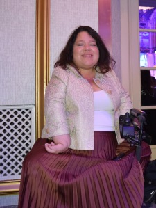 A woman with shoulder-length brown hair smiling brightly and posing in her electric wheelchair. She is wearing an ivory jacket and maroon pleated skirt.