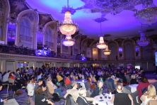 An ornate hotel ballroom filled with people standing and sitting in rows, around round tables, and at cocktail tables.