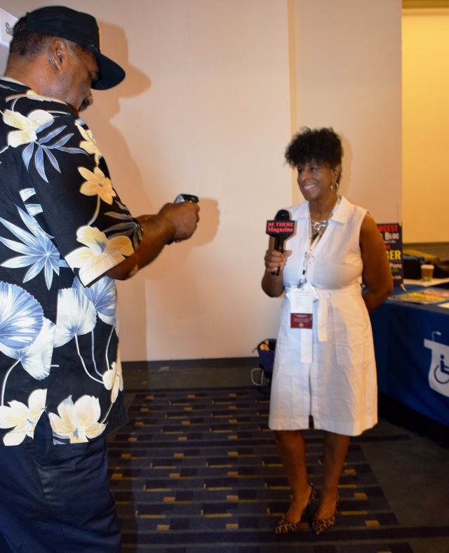 A Black woman wearing a white dress and leopard print high heels smiles and holds a microphone. A Black man wearing a floral print shirt and a black baseball cap stands in front of her, holding up his cell phone to record her.