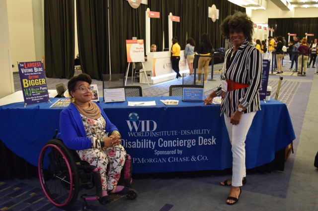 2 Black women smiling in front of the WID desk. Luticha is wearing a blue blazer and floral jumpsuit with pink flowers that match her pink wheelchair. Cathy stands next to her, wearing a black and white striped shirt and white pants with a red belt.