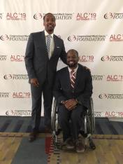 2 black men wearing suits pose in front of a backdrop covered in CBCF logos. Eric (right) uses a wheelchair and his brother stands with his arm around Eric's shoulder.