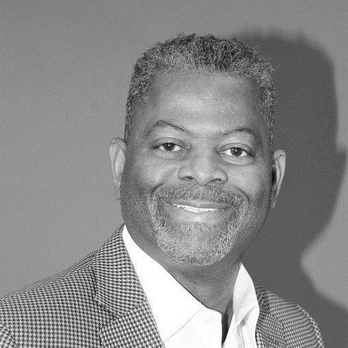A black man wearing a houndstooth checked suit smiling into the camera.