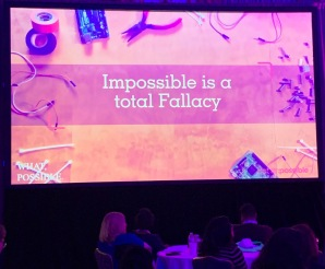 "Large screen with the words, ""Impossible is a total fallacy"" over image of worktable with wires and fasteners."