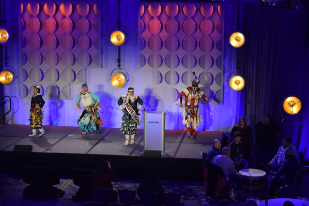 4 dancers in elaborate beaded costumes dancing on stage, a circle of 5 drummers playing off to the right side.