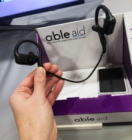 Able Aid sound amplifying headset, with earbuds connected by over the ear cords, a small black box connecting the earbud to the cords. Held in hand for scale, black boxes about the size of a thumb. Packaging has able aid logo with slogan: able to hear the laughter from today forward.