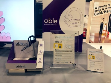 Able Aid sound amplifying headset, with earbuds connected by over the ear cords. Sign with able aid logo with slogan: evolved sound for you.