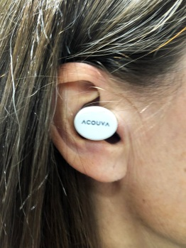 Small white plastic insertable in-ear hearing device from Acouva.