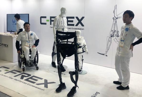 Several exhibitors in white lab suits with C-FREX (Carbon Fiber Reinforced Exoskeleton) logo. Sleek black exoskeleton wearing black Nike shoes.
