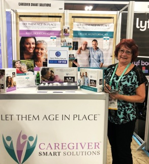 Exhibitor standing with Let Them Age In Place Caregiver Smart Solutions booth.