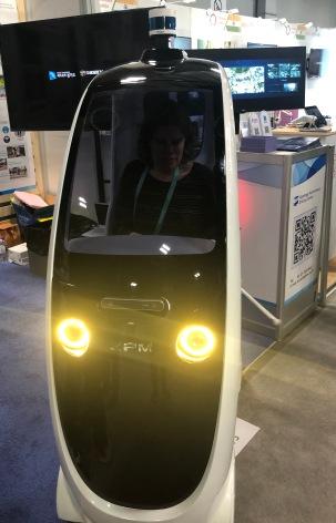 Front view of pod-like vehicle, headlights shining through sleek black and white plastic.