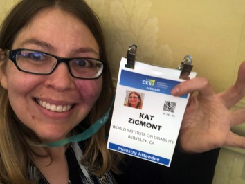 WID's Operations Director Kat holding up her CES attendee badge and smiling.