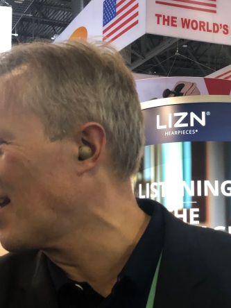 Exhibitor demonstrating the Lizn Hearpiece in-ear hearing aid.