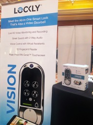 Sign reads: Lockly - meet the all-in-one smart lock that's also a video doorbell. Live HD video monitoring and recording, greet guests with 2 way audio, voice control with virtual assistants, 3D fingerprint reader, peek-proof PIN Genie touchscreen.