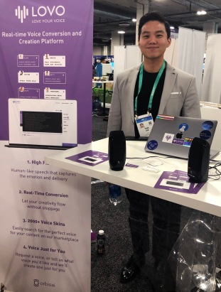 Exhibitor with sign, reads: Lovo love your voice real-time voice conversion and creation platform.