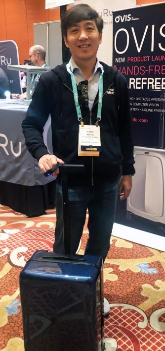 Exhibitor standing behind an Ovis smart luggage bag, wearing the corresponding smart bracelet.